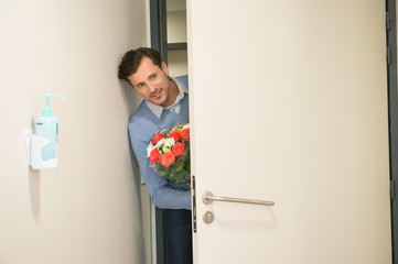 Man peeking through an open door with a bouquet of flowers in hospital room