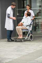 Male doctor talking to a female patient sitting in a chair
