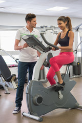 Trainer helping a woman with the cycle in a gym