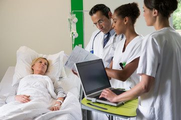 Medical team discussing female patient record on hospital bed