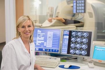 Female doctor smiling in medical MRI scan monitor room