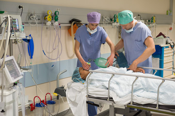 Doctor and nurse giving oxygen to patient in recovery room