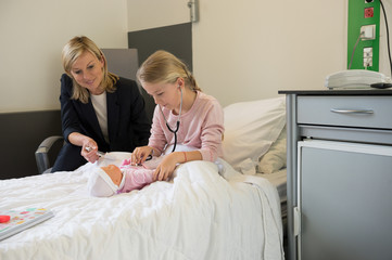 Girl examining a doll with stethoscope and her mother sitting beside her in hospital