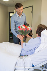 Man giving his mother a bouquet of flowers in hospital bed