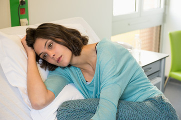 Female depressed patient lying on the bed in a hospital ward