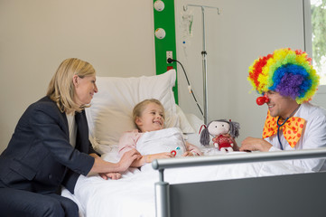 Male doctor wearing clown costume making girl patient smile in hospital bed