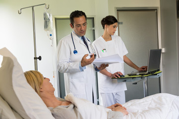 Male doctor giving pills instructions to female patient in hospital bed