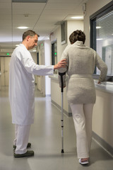 Male doctor assisting female patient on crutches in hospital