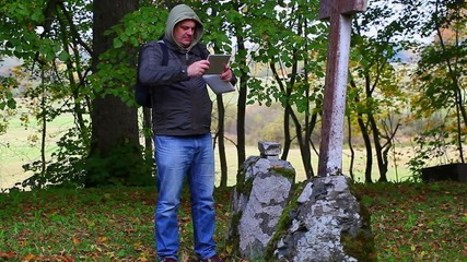 Hiker with tablet PC near old stone crosses