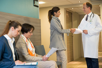 Male doctor shaking hands with his patient in waiting room