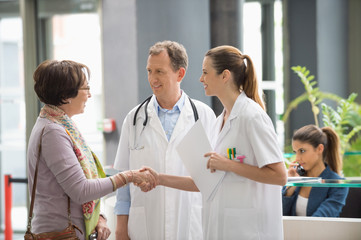 Doctor shaking hands with his patient at hospital reception desk