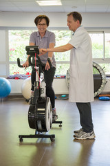 Physical therapist helping a patient to ride an exercise bike