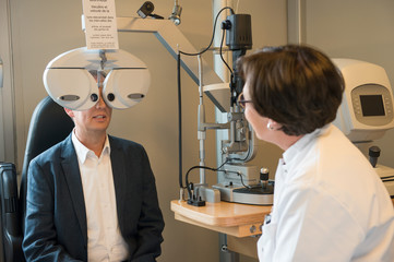 Female optometrist examining man's eyes