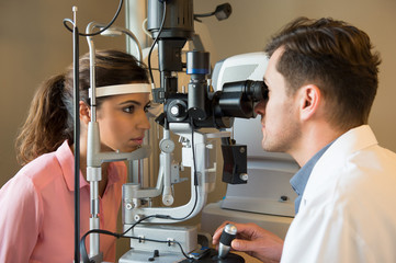 Male optometrist examining woman's eyes