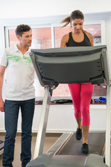 Instructor teaching a woman on a treadmill in a gym