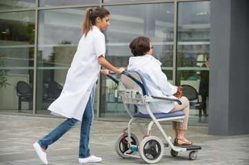 Female doctor pushing a patient sitting in a chair