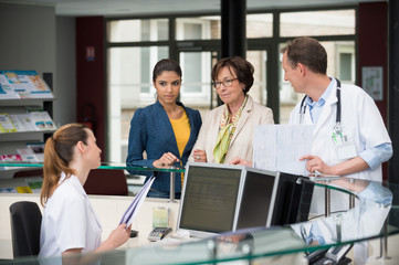 Patients discussing with receptionist at hospital reception desk