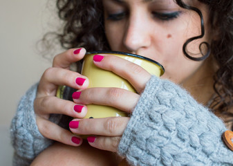 Young woman drinking coffee at home in winter