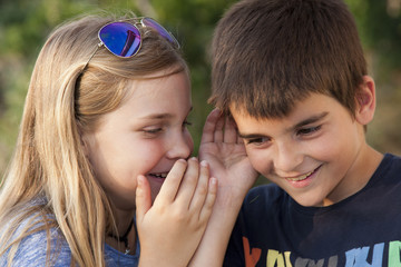 boy and girl counting a secret to the ear