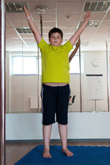 Boy does exercise  in the gym