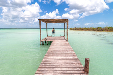 pier and woman in Bacalar lagoon, Mexico