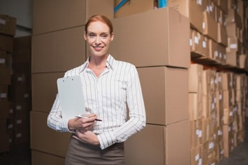 Female manager with clipboard in warehouse