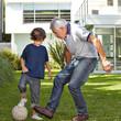 Kind spielt mit Opa Fußball im Garten