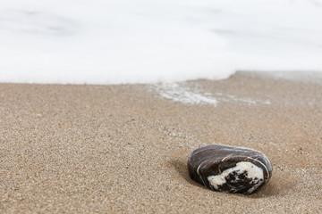Einzelner Stein am Strand