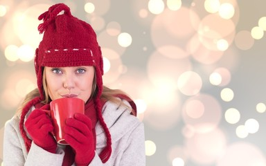 Composite image of happy blonde in winter clothes holding mug