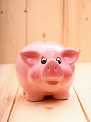 Funny pink piggy bank on wood background