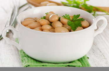 Beans with fresh parsley   on  a wooden table.