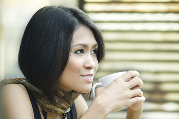 Attractive Asian Woman enjoys her drink
