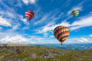 Three big multi-colored balloons in the blue sky over mountains