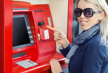 Woman using ATM to withdraw cash