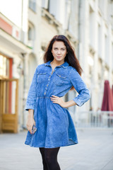 Young woman in blue jeans dress on the street