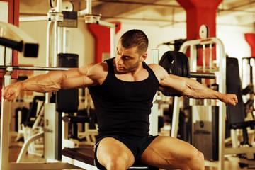 bodybuilder training gym, tensing arms