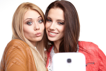 portrait of two beautiful girls making selfies at studio