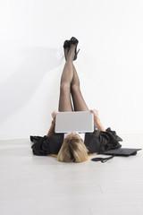 Female University student laying on floor using laptop