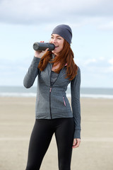 Athletic female drinking water from bottle outdoors