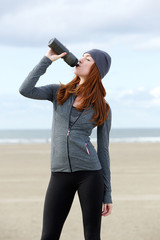 Young sports woman drinking water from bottle outdoors