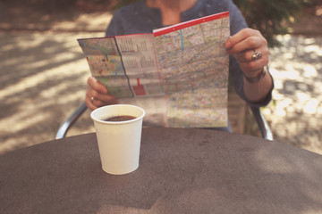 Elderly woman studying map and having coffee