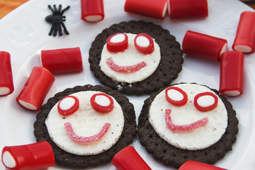 Smiling cookies with candies and spiders in Halloween festivitie
