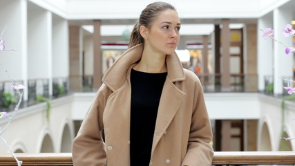 Young beautiful girl looks in a shopping center.