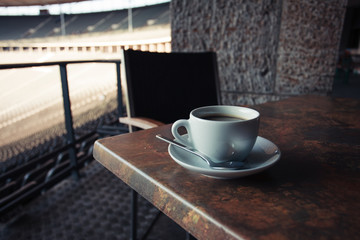 Cup of coffee on table in stadium