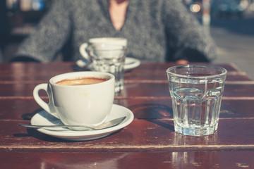 Elderly woman drinking coffee outside