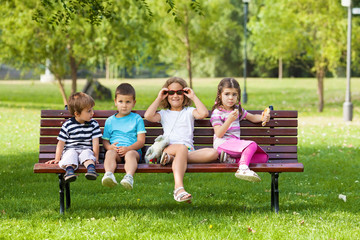 Playful group of children sitting on a bench in nature