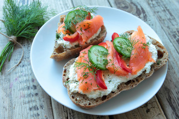 Sandwich with salmon cheese and vegetables for breakfast