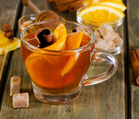 Christmas tea with orange, honey and spices on a  wooden table