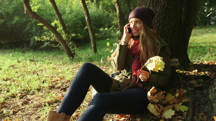 Young pretty woman sitting in autumn park with phone.