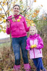 mother and her daughter with autumnal apple tree